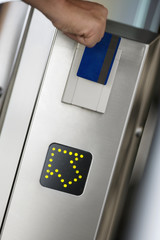 Person swiping card in entrance barrier, guided by arrow sign, close-up, rear view (tilt)