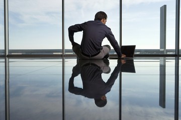 Reflection of businessman sitting on floor near window, using laptop, rear view, surface level