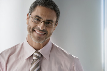 Mature businessman wearing spectacles, smiling, front view, portrait