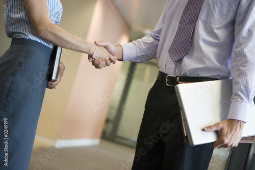 Businessman and businesswoman shaking hands in office corridor, side view, mid-section (tilt)