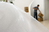 Man sealing box with tape at home, focus on bubble wrap in foreground