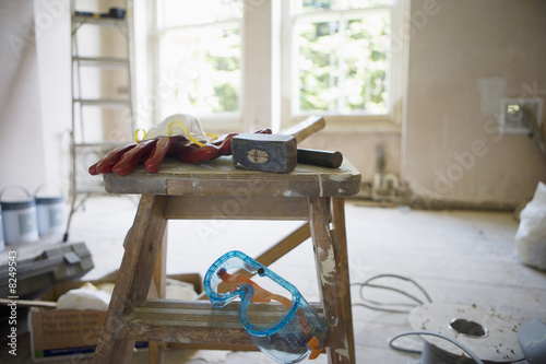 Various work tools on top of step ladder in undecorated room in house