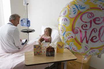 Girl (7-9) sitting in hospital bed, talking to doctor, balloon and cards in foreground, side view