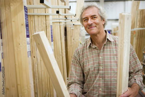 Senior man shopping for timber in DIY shop, smiling, portrait