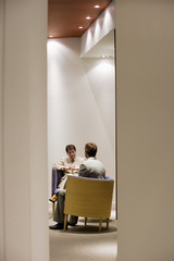 Two businessmen sitting in meeting room having private conversation, view through doorway
