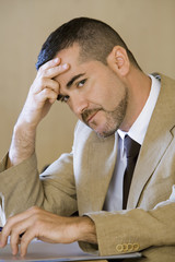 Stressed businessman tapping fingers on desk, leaning head on hand, side view, close-up, portrait