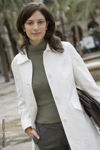 Businesswoman in polo neck top and white coat standing in plaza, carrying briefcase, portrait (tilt)