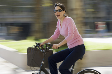 Woman in sunglasses cycling with briefcase in urban area, smiling, side view (blurred motion)