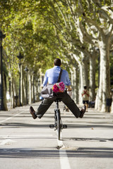 Man cycling on treelined path with legs apart, carrying bag and bouquet of pink flowers, rear view