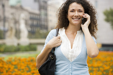 Woman using mobile phone, carrying shoulder bag, smiling, portrait, orange flowers in background