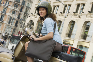 Spain, Barcelona, woman in crash helmet riding moped in city street, carrying bag, portrait (tilt)
