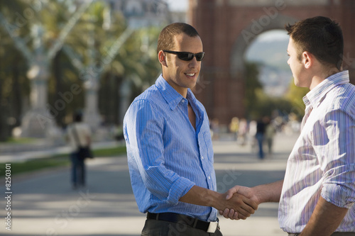 Spain, Barcelona, two businessmen shaking hands, smiling, side view