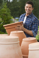 Man shopping for plant pots in garden centre, smiling, side view, portrait