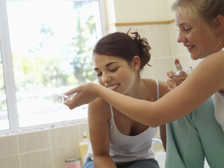 Teenage girl (15-17) smelling perfume on friend's wrist in bathroom, smiling (tilt)