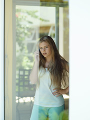 Teenage girl (15-17) looking through window at home, using mobile phone, hand on hip, portrait