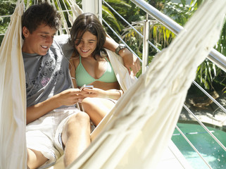 Teenage couple (15-17) relaxing in hammock on balcony, listening to MP3 player, smiling