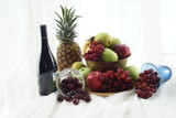 Red wine with pineapple and overflowing brass fruit bowl.