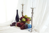 Candlesticks, red wine and brass fruit bowl