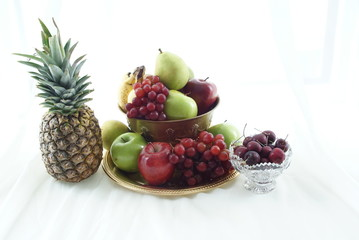 bowl of fruit with pineapple and bowl of cherries on the side