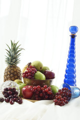 Blue glass bottle with pineapple and brass fruit bowl.
