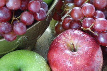 Closeup image of red and green apples and red grapes.