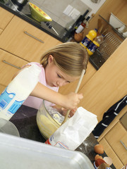 Girl (6-8) standing in kitchen, mixing flour, eggs and milk in glass bowl with wooden spoon (tilt)