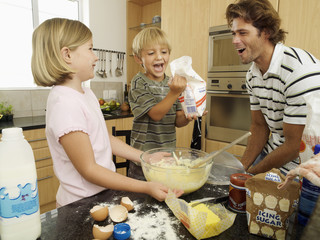 Father and two children (5-8) making cake mix in kitchen, boy holding bag of flour, laughing