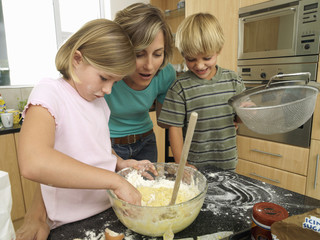 Mother and children (5-8) making cake mix in kitchen, boy holding sieve, girl dipping hand in bowl
