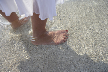 Woman standing on beach, ankle deep in sea water, low section, focus on feet, close-up, side view