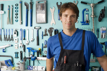 Man standing in front of display rack in tool shop, smiling, front view, portrait
