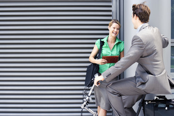 Businessman cycling on folding commuter bicycle flirting with businesswoman standing on pavement