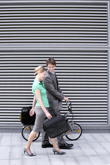 Businessman walking with businesswoman on pavement, man pushing folding commuter bicycle