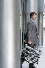 Businessman leaving office building, carrying folding commuter bicycle, side view