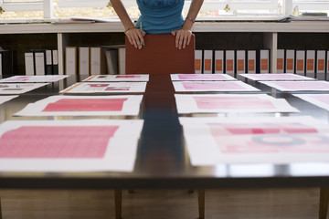 Woman looking at various designs arranged on large table in office, surface level