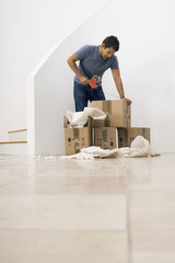 Man moving house, using duct tape dispenser to seal box, standing in sparse room, surface level