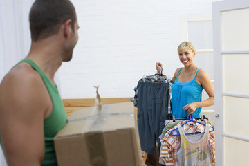 Couple moving house, woman packing clothing in bedroom, man carrying sealed box, smiling
