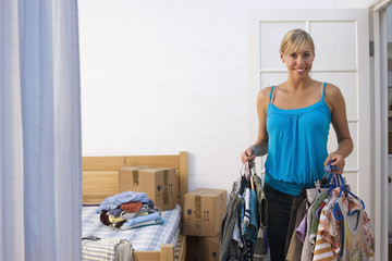 Woman moving house, packing clothing in bedroom, smiling, portrait