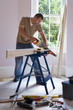 Man doing DIY at home, cutting plank of wood on workbench with saw, side view