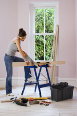 Woman doing DIY at home, cutting plank of wood on workbench with saw, side view