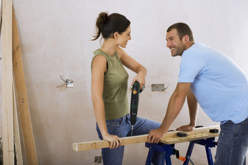 Couple doing DIY at home, woman drilling hole with power drill on workbench, man assisting, smiling