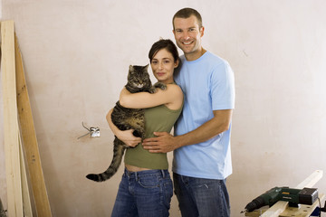 Couple doing DIY at home, woman holding domestic cat, man embracing woman, smiling, portrait