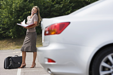 Businesswoman standing in car park, reading document in folder, using mobile phone, smiling