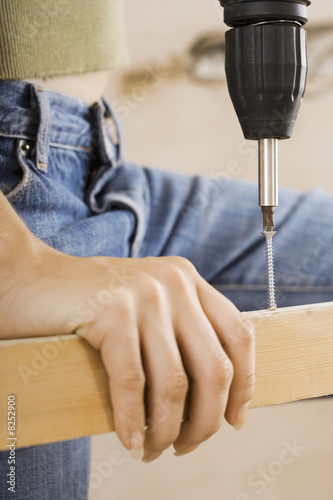Woman doing DIY at home, drilling hole in timber with power drill, close-up, mid-section