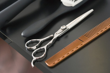 Hairdressing scissors, hairbrush and comb on tray, close-up (still life)