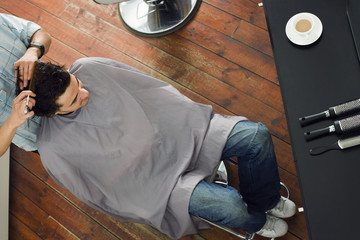Hairdresser combing man's hair in barber shop, overhead view