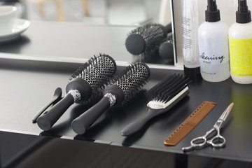 Hairbrushes, hair products, comb and scissors arranged on table in salon, close-up (still life)