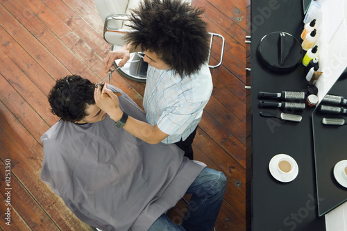 Young male hairdresser cutting man's hair in barber shop, overhead view