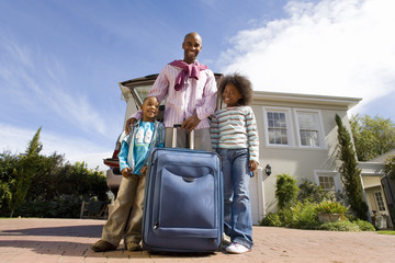 Father with son and daughter(8-10) holding suitcase outdoors by house, smiling, portrait, low angle view