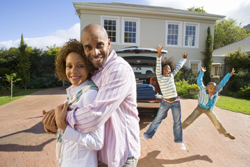 Couple embracing outdoors by house and car, two children jumping in air in background, smiling, portrait