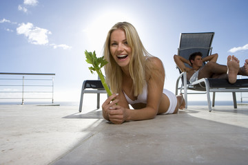 Young woman with celery by man on sun bed, smiling, portrait, close-up